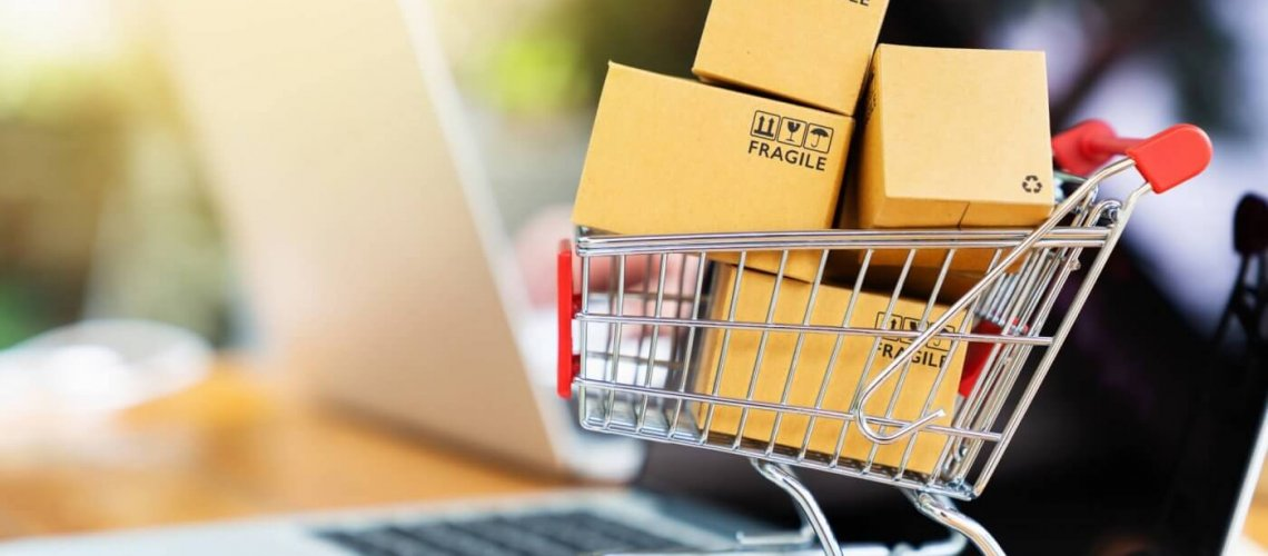 Package boxes in cart with laptop computer for online shopping concept